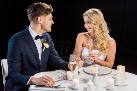 glückliches junges Paar, das mit Champagnergläsern am gedeckten Tisch sitzt und sich isoliert auf schwarz anschaut