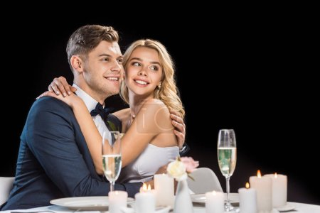 happy groom and bride embracing while sitting at served table isolated on black