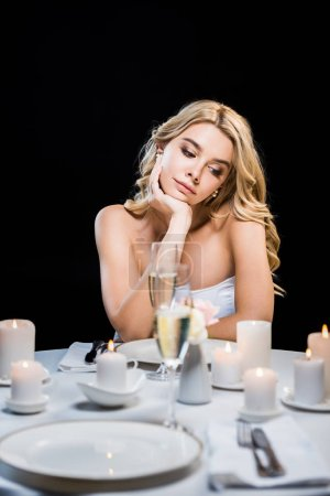 Photo for Selective focus of beautiful dreamy young woman sitting by served table alone isolated on black - Royalty Free Image