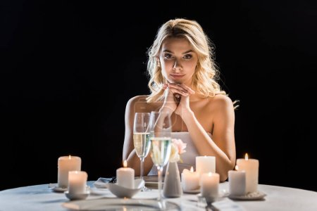 beautiful young bride sitting alone at table with burning candles isolated on black