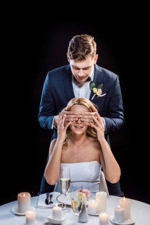 Photo pour Jeune groom debout derrière la mariée séance, fermant ses yeux avec les mains isolées sur fond noir - image libre de droit