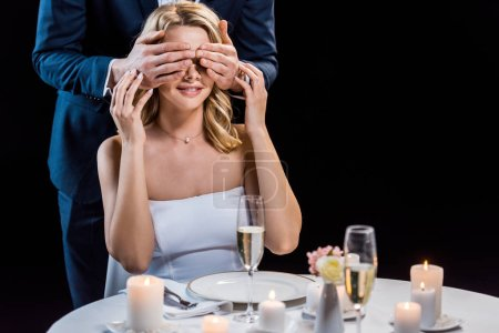Photo for Cropped view of groom standing behind sitting bride and closing her eyes with hands isolated on black - Royalty Free Image