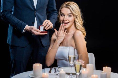Photo pour Vue partielle de l'homme faisant la demande en mariage à amusé jeune femme isolée sur noir - image libre de droit