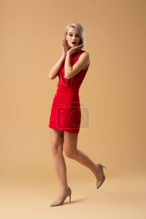 Photo pour Surpris blonde jeune femme en robe rouge permanent sur fond beige - image libre de droit