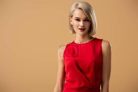 Foto de Elegante mujer joven rubia en vestido rojo mirando a la cámara aislada en beige - Imagen libre de derechos