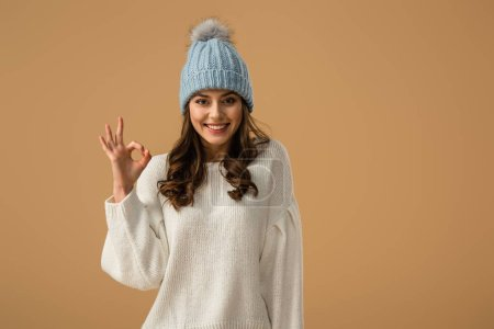 Glad smiling girl in knitted hat showing okay sign isolated on beige