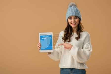 Photo for Smiling brunette woman in white sweater pointing with finger at digital tablet with twitter app on screen isolated on beige - Royalty Free Image