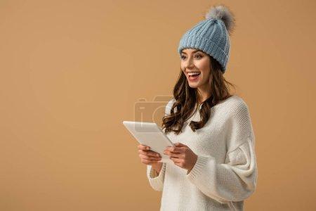 Photo pour Superbe fille bouclée en bonnet tenant la tablette numérique et rire isolé sur beige - image libre de droit