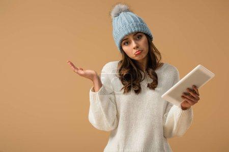 Photo pour Triste jeune femme en bonnet tricoté tenant tablette numérique isolée sur beige - image libre de droit