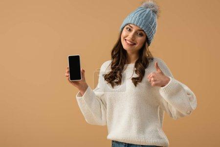 Photo pour Fille heureuse en pull blanc tenant smartphone avec écran blanc et montrant pouce vers le haut isolé sur beige - image libre de droit