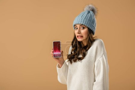 Photo for Confused brunette girl in hat holding smartphone with trading courses app on screen isolated on beige - Royalty Free Image