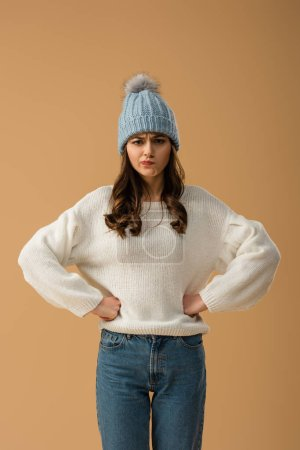 Photo for Skeptical brunette girl in white sweater standing with arms akimbo isolated on beige - Royalty Free Image