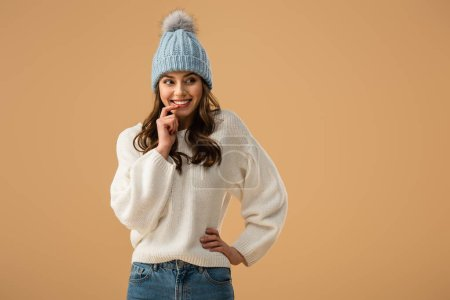 Photo for Cheerful brunette woman in knitted hat touching lip with finger and looking away isolated on beige - Royalty Free Image