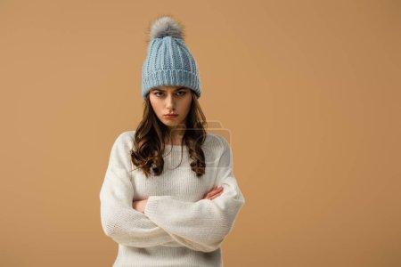 Photo pour Contrarié femme brune en termes de bonnet tricoté avec bras croisés isolé sur beige - image libre de droit