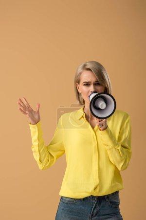 Photo pour Femme blonde inquiète en chemise jaune parlant en mégaphone isolé sur beige - image libre de droit