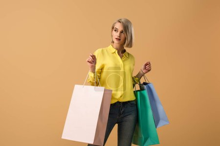 Photo pour Jeune fille blonde songeuse en chemise jaune, portant des sacs shopping isolés sur beige - image libre de droit