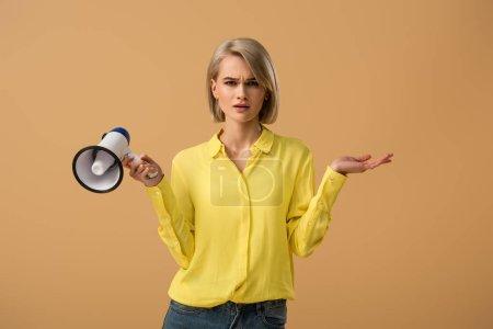 Photo pour Fille blonde confus en chemise jaune tenant haut-parleur isolé sur beige - image libre de droit