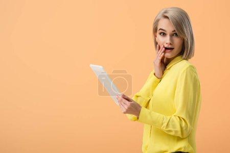 schockierte blonde Frau in gelbem Hemd mit digitalem Tablet auf orangefarbenem Hintergrund