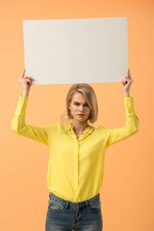 Photo for Dissatisfied blonde girl in yellow shirt holding blank placard isolated on orange - Royalty Free Image
