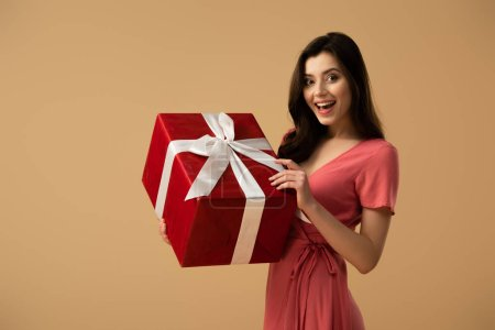 Photo for Surprised brunette girl in dress holding red gift box and smiling isolated on beige - Royalty Free Image