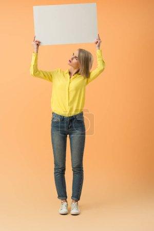 Photo pour Pleine longueur vue de fille blonde irritée en jeans tenant une pancarte vierge sur fond orange - image libre de droit