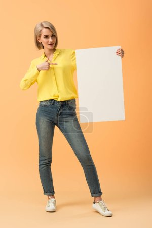 Photo for Confident blonde girl in jeans pointing with finger at blank placard on orange background - Royalty Free Image