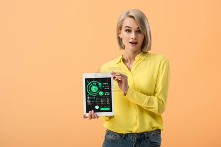 Photo for Surprised blonde girl holding digital tablet with infographic app on screen isolated on orange - Royalty Free Image
