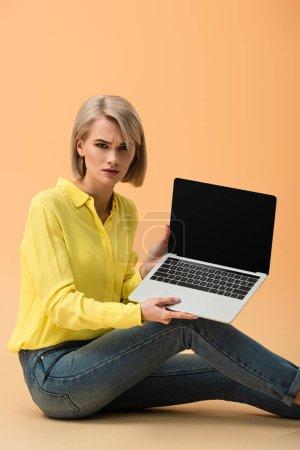 Photo pour Femme blonde bouleversée en chemise jaune montrant ordinateur portable avec écran blanc sur fond orange - image libre de droit