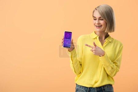 Femme blonde souriante pointant du doigt le smartphone avec l'application de magasinage en ligne à l'écran isolé sur orange