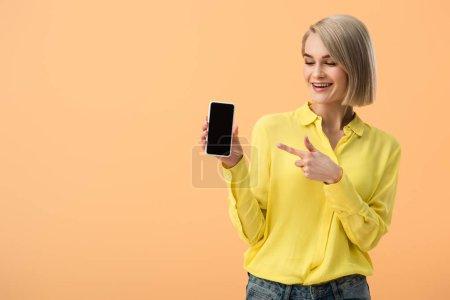 Photo pour Femme souriante en chemise jaune pointant du doigt le smartphone avec écran blanc isolé sur orange - image libre de droit