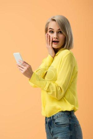 Photo for Stylish surprised blonde girl holding smartphone isolated on orange - Royalty Free Image