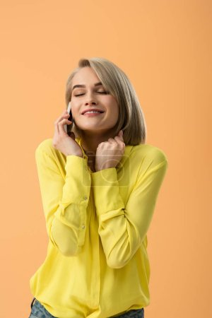 Photo for Inspired blonde girl in yellow shirt talking on smartphone with closed eyes isolated on orange - Royalty Free Image