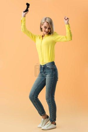 Photo pour Souriant joystick holding jeune fille blonde et dansant sur fond orange - image libre de droit