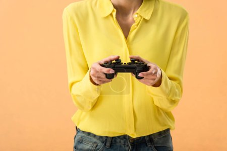 Photo for Cropped view of woman in yellow shirt holding gamepad isolated on orange - Royalty Free Image
