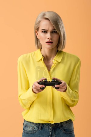 Photo pour Femme blonde inquiète en chemise jaune tenant la manette isolé sur orange - image libre de droit