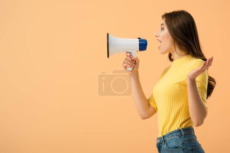 Photo pour Vue latérale de jolie femme brune criant dans haut-parleur isolé sur orange - image libre de droit