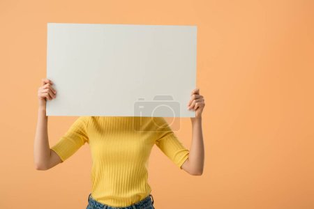 Photo for Young woman in yellow jumper holding blank placard isolated on orange - Royalty Free Image