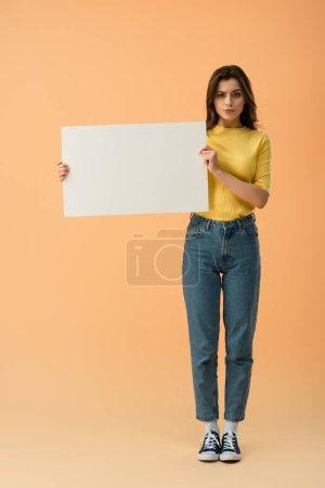 Pensive brunette girl in jeans and jumper holding blank placard on orange background