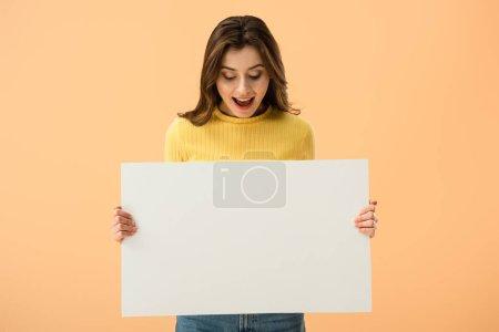 Photo pour Jeune femme brune excitée tenant une pancarte vierge et riant isolé sur orange - image libre de droit