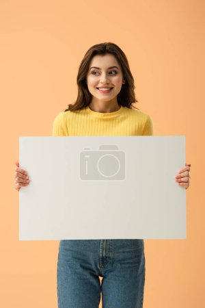 Photo for Blissful smiling brunette girl holding blank placard isolated on orange - Royalty Free Image