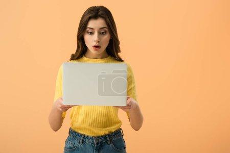 Photo pour Choqué brune jeune femme tenant portable isolé sur orange - image libre de droit