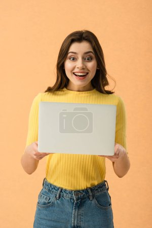 Photo for Surprised brunette girl holding laptop and smiling isolated on orange - Royalty Free Image