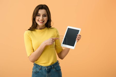 Smiling brunette girl pointing with finger at digital tablet with blank screen isolated on orange