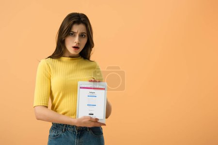 Photo for Shocked brunette girl holding digital tablet with instagram app on screen isolated on orange - Royalty Free Image