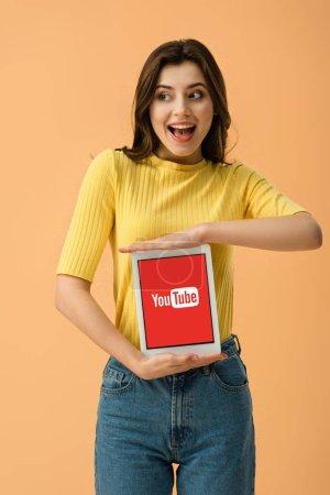 Foto de Excitada a chica morena sosteniendo digital tablet con la app de youtube en pantalla aislada en naranja - Imagen libre de derechos