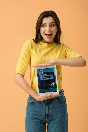 Excited brunette girl holding digital tablet with booking app on screen isolated on orange