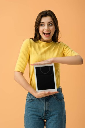 Photo for Excited young woman holding digital tablet with blank screen isolated on orange - Royalty Free Image