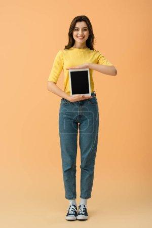 Photo pour Vue pleine longueur de fille souriante en jeans tenant tablette numérique avec écran blanc sur fond orange - image libre de droit