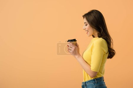 Photo for Side view of brunette girl holding paper cup with coffee isolated on orange - Royalty Free Image