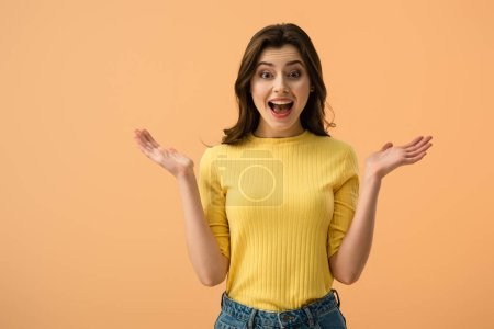 Photo for Surprised brunette woman gesturing while standing  isolated on orange - Royalty Free Image
